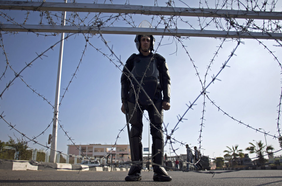 Photo - A policeman stands guard outside a courthouse during the trial of Egypt's toppled President Mohammed Morsi in Cairo, Egypt, Tuesday, Jan. 28, 2014. Morsi has arrived in Cairo for the start of his trial Tuesday over charges he and some 130 others face for prison breaks during the country's 2011 revolution, the state news agency reported. (AP Photo/Khalil Hamra)