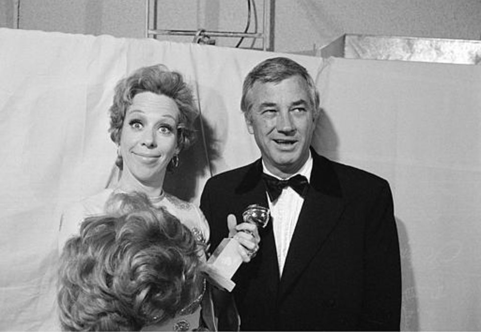"Comedy star Carol Burnett, accompanied by her husband and producer Joe Hamilton, is seen clowning backstage, holding her Golden Globe in one hand and a wig in the other, at the Golden Globe Awards in Los Angeles, Calif., February 6, 1971. Burnett received the award in the category ""Best Television Show - Musical/Comedy.""  (AP Photo)"