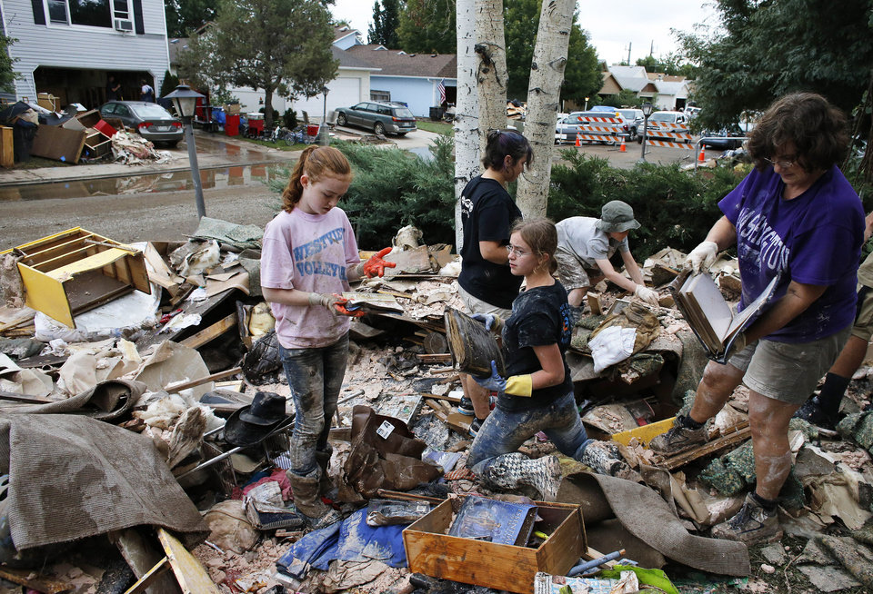 Photo - Katie Byrne, left, her neighbor Elizabeth Dipert, center, and church volunteer Linda Pekarek, right, sift through thrown out rotting flood refuse looking for valuables, at Byrne's home in Longmont, Colo., Wednesday Sept. 18, 2013. Statewide, only about 22,000 homeowners have flood insurance policies, FEMA spokesman Jerry DeFelice said. With 2.2 million housing units in Colorado, according to Census figures, that means about 1 percent of the state's residences have flood coverage. (AP Photo/Brennan Linsley)
