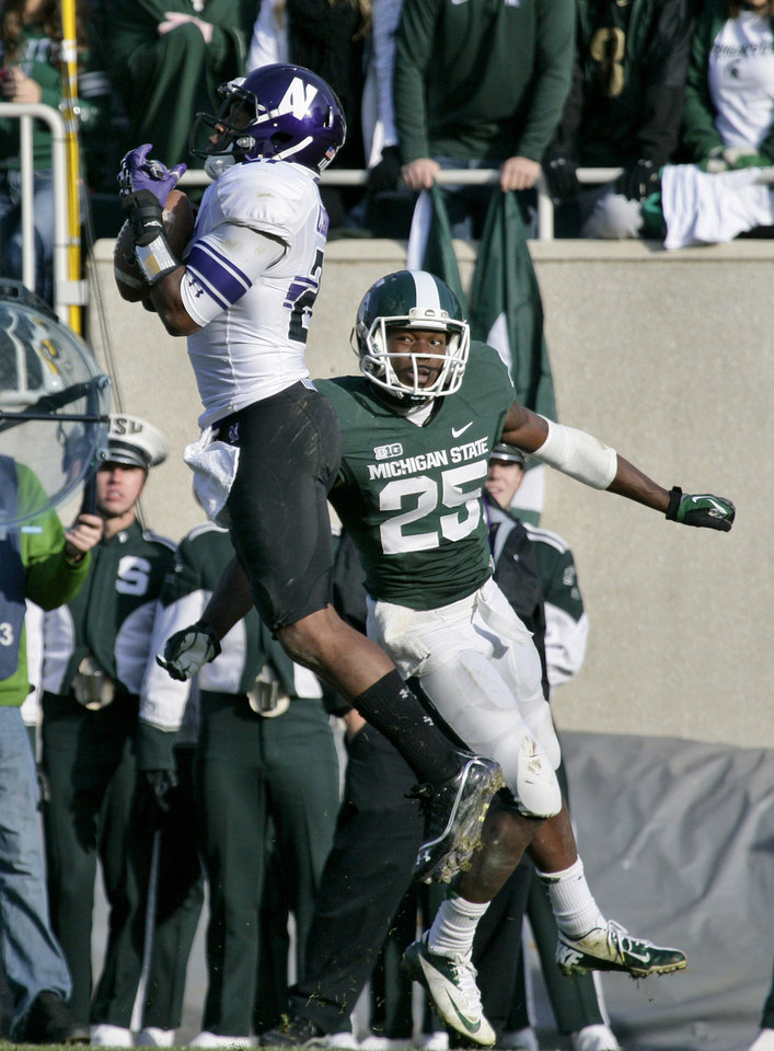 Photo -   Northwestern's Jared Carpenter, left, intercepts a pass intended for Michigan State's Keith Mumphery (25) during the third quarter of an NCAA college football game, Saturday, Nov. 17, 2012, in East Lansing, Mich. Northwestern won 23-20. (AP Photo/Al Goldis)