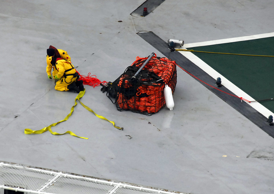 Photo - A photo provided by the U.S. Coast Guard shows a salvage team wrapping up lines from an emergency towing system delivered to the deck of the petroleum drilling ship Kulluk  Wednesday, Jan. 2, 2013, in the Gulf of Alaska. The grounding of the drill ship on a remote Alaska island has refueled the debate over oil exploration in the U.S. Arctic Ocean. (AP Photo/U.S. Coast Guard)