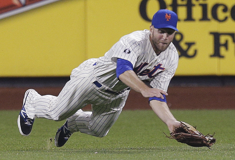 Photo - New York Mets first baseman Eric Campbell makes a diving catch on a ball hit by Los Angeles Dodgers' Hanley Ramirez during the eighth inning of a baseball game, Thursday, May 22, 2014, in New York. Yasiel Puig was caught off second base for a double play. (AP Photo/Julie Jacobson)