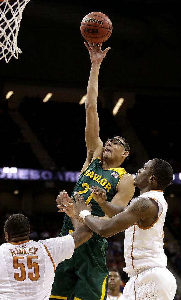 Photo - Baylor's Isaiah Austin (21) shoots over Texas' Cameron Ridley (55) and Kendal Yancy during the first half of an NCAA college basketball game in the semifinals of the Big 12 Conference tournament on Friday, March 14, 2014, in Kansas City, Mo. (AP Photo/Charlie Riedel)