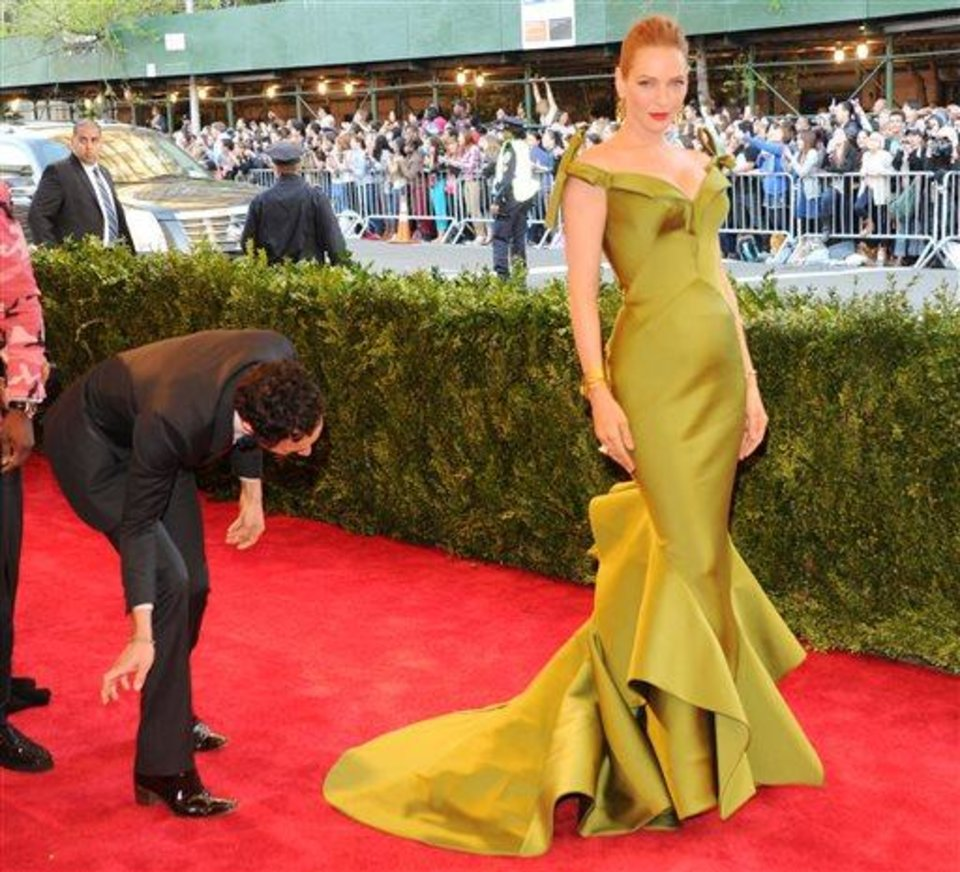 Photo - Designer Zac Posen, left, fixes the dress of actress Uma Thurman as they attend The Metropolitan Museum of Art's Costume Institute benefit celebrating