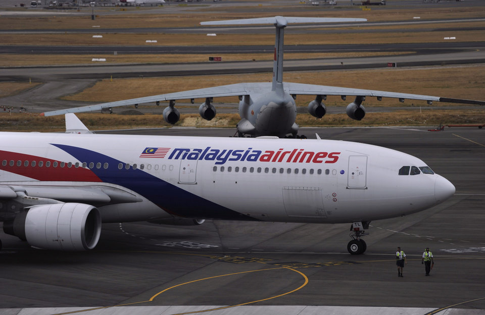 Photo - A Malaysia Airlines plane, foreground, prepares to go out onto the runway and passes by a stationary Chinese Ilyushin 76 aircraft at Perth International Airport  in Perth, Australia, Tuesday, March 25, 2014. Malaysia said Tuesday that it has narrowed the search for a downed jetliner to an area the size of Texas and Oklahoma in the southern Indian Ocean, while Australia said improved weather would allow the hunt for possible debris from the plane to resume. (AP Photo/Greg Wood, Pool)