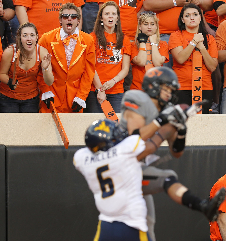 Photo - OSU fans watch as Oklahoma State's Charlie Moore (17) catches a touchdown pass against West Virginia's Pat Miller (6) in the third quarter during a college football game between Oklahoma State University (OSU) and West Virginia University (WVU) at Boone Pickens Stadium in Stillwater, Okla., Saturday, Nov. 10, 2012. OSU won, 55-34. Photo by Nate Billings, The Oklahoman
