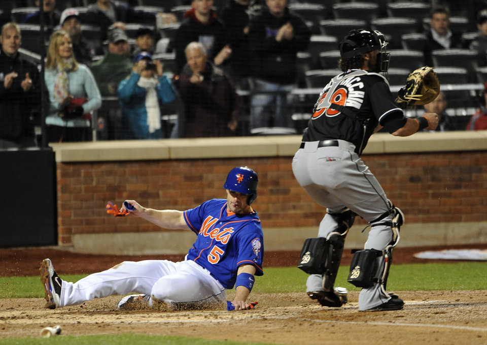 Photo - New York Mets' David Wright, left, scores at home plate past Miami Marlins catcher Jarrod Saltalamacchia on a double hit by Daniel Murphy in the third inning of a baseball game at Citi Field on Friday, April 25, 2014, in New York. (AP Photo/Kathy Kmonicek)