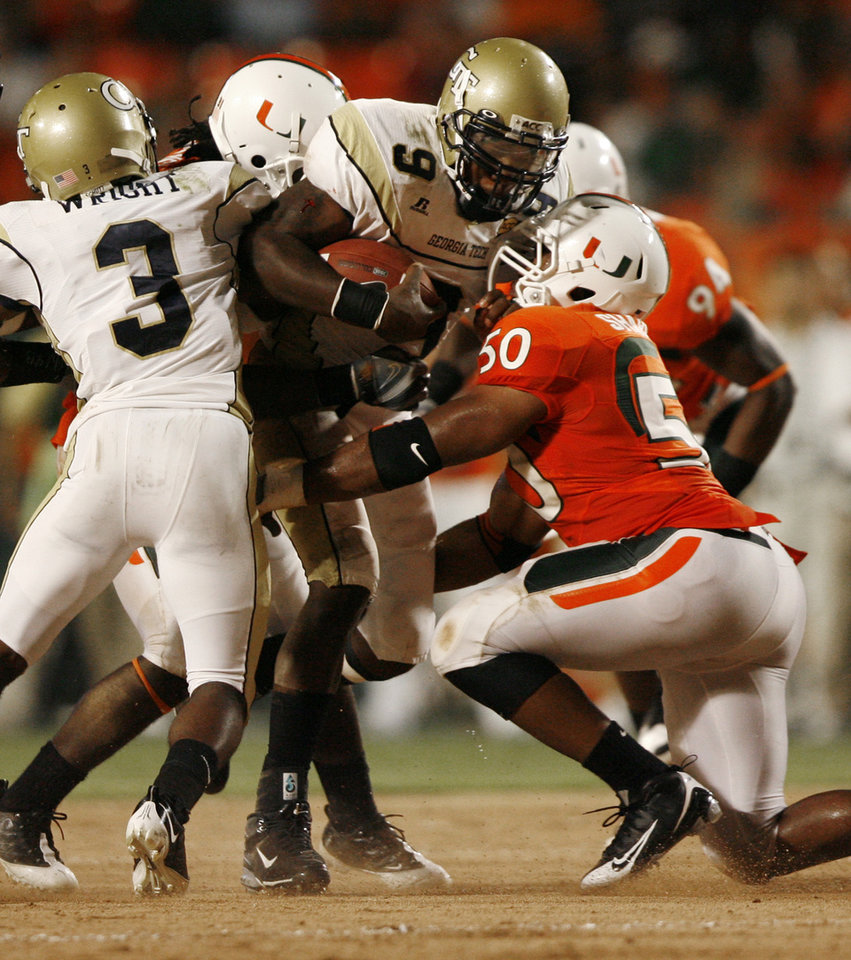 Photo - Georgia Tech University quarterback Josh Nesbitt (9) is tackled by University of Miami's Darryl Sharpton (50) during the second quarter of an NCAA college football game Thursday, Sept. 17, 2009, in Miami. (AP Photo/Hans Deryk) ORG XMIT: LSS107