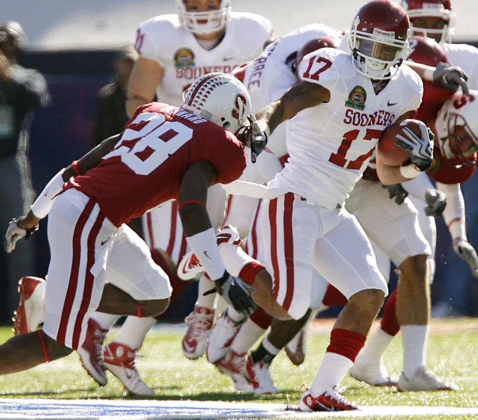 Oklahoma's Mossis Madu (17) runs past Stanford's Harold Bernard (28) during the first half of the Brut Sun Bowl college football game between the University of Oklahoma Sooners (OU) and the Stanford University Cardinal on Thursday, Dec. 31, 2009, in El Paso, Tex.   Photo by Chris Landsberger, The Oklahoman