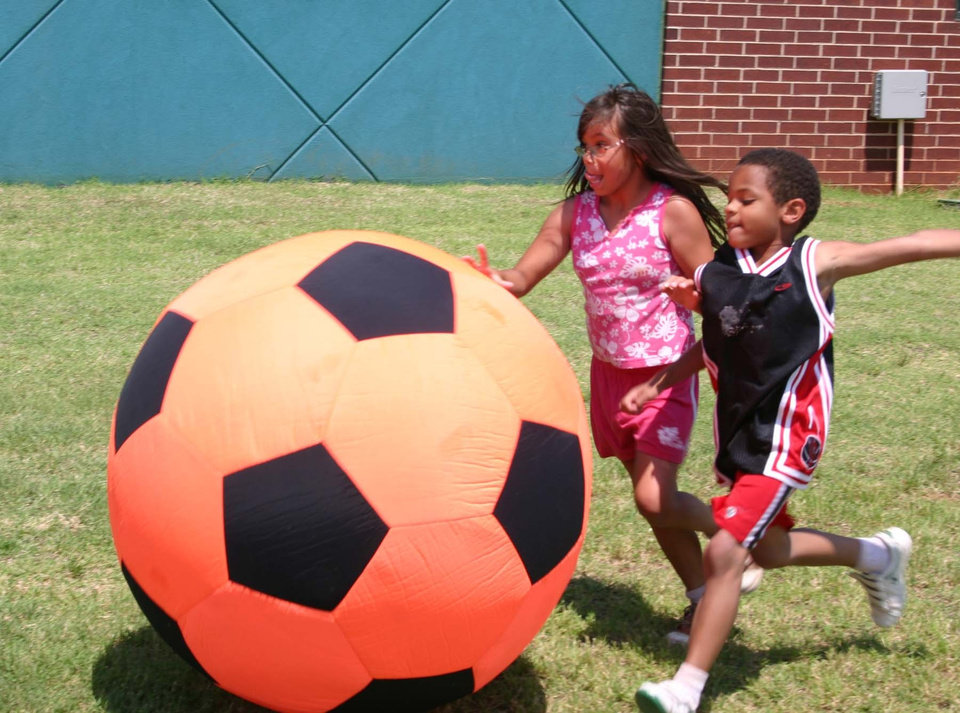 Summer day campers Chelle Seal (left) and Tyler Santiago, both of Noble, race to the soccer ball as they play giant soccer at the Movin' & Groovin' summer day camp at the J. D. McCarty Center in Norman. Giant soccer was just one of many sports and games the campers participated in during the week long camp.<br/><b>Community Photo By:</b> Greg Gaston<br/><b>Submitted By:</b> Greg,