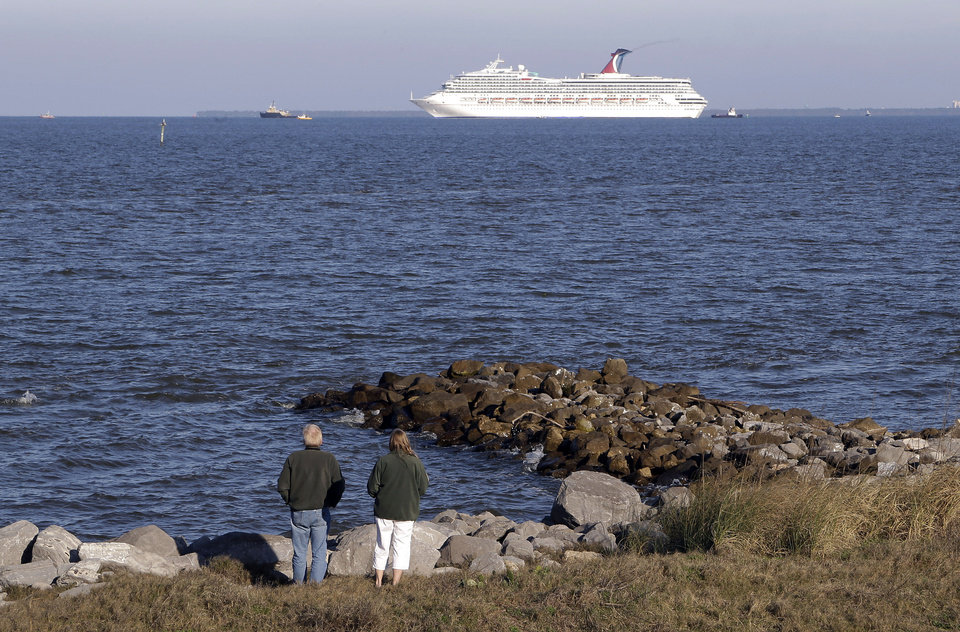 Photo - People watch the cruise ship Carnival Triumph as it is towed into Mobile Bay from Dauphin Island, Ala., Thursday, Feb. 14, 2013. The ship with more than 4,200 passengers and crew members has been idled for nearly a week in the Gulf of Mexico following an engine room fire. (AP Photo/Dave Martin)