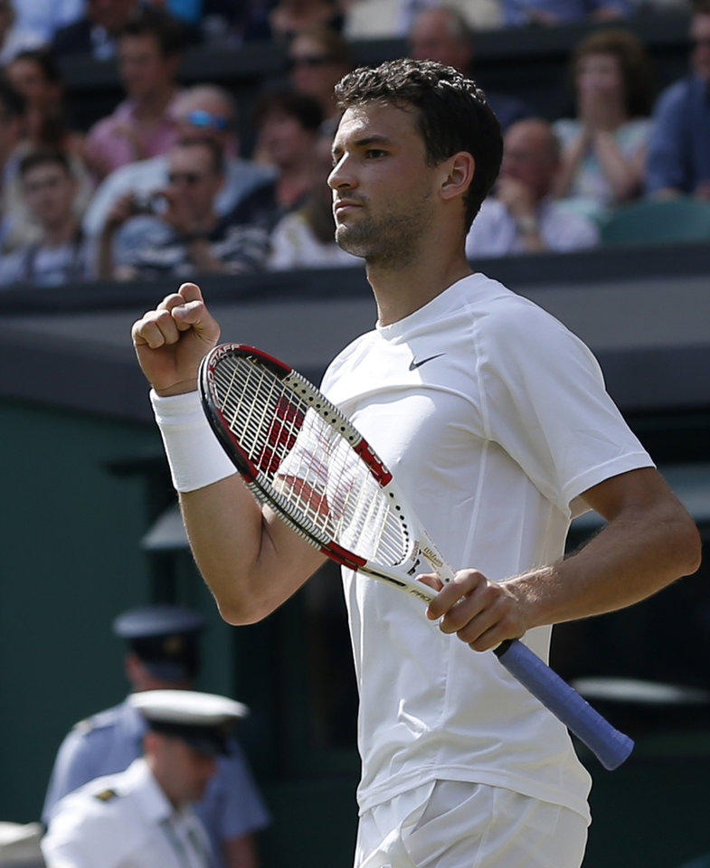 Photo - Grigor Dimitrov of Bulgaria celebrates after defeating defending champion Andy Murray of Britain in their men's singles quarterfinal match at the All England Lawn Tennis Championships in Wimbledon, London, Wednesday, July 2, 2014. (AP Photo/Pavel Golovkin)