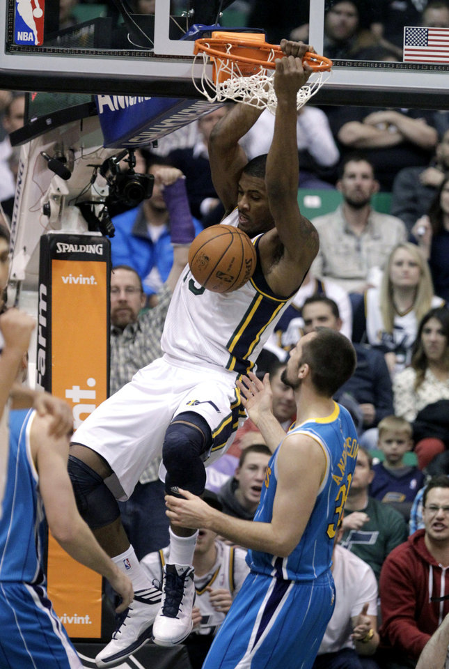 Utah Jazz's Derrick Favors (15) dunks the ball as New Orleans Hornets' Ryan Anderson (33) watches in the second quarter during an NBA basketball game Wednesday, Jan. 30, 2013, in Salt Lake City. (AP Photo/Rick Bowmer)