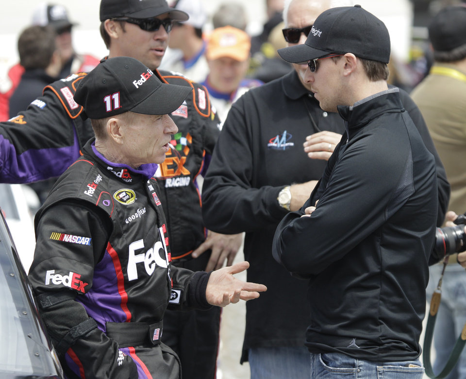 Mark Martin, left, talks with Denny Hamlin, right, before the STP 500 NASCAR Sprint Cup series auto race at Martinsville Speedway in Martinsville, Va., Sunday April 7, 2013. (AP Photo/Steve Helber)