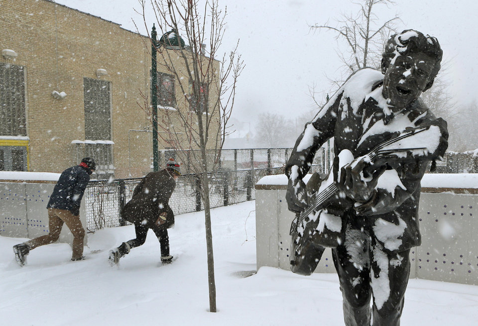 Photo - Two people duck into the blowing snow as they leave the U City Loop next to the statue of Chuck Berry on Sunday morning, Jan. 5, 201, in St. Louis.  Heavy snow combined with strong winds and bitter cold created a dangerous winter mix Sunday over much of Missouri. (AP Photo/St. Louis Post-Dispatch, J.B. Forbes )  EDWARDSVILLE INTELLIGENCER OUT; THE ALTON TELEGRAPH OUT