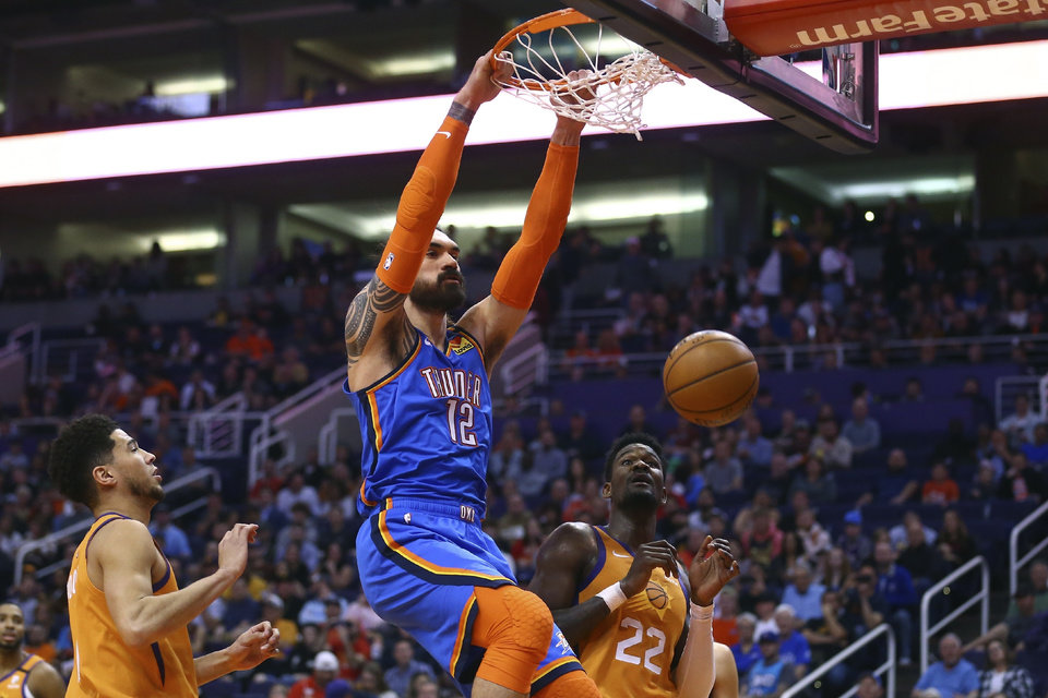 Photo - Oklahoma City Thunder center Steven Adams (12) dunks as Phoenix Suns guard Devin Booker, left, and center Deandre Ayton (22) watch during the first half of an NBA basketball game Friday, Jan. 31, 2020, in Phoenix. (AP Photo/Ross D. Franklin)