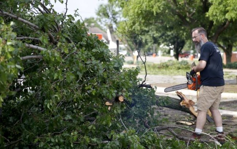 Photo -  Greg Bellah cleans up tree damage in the  Trinity Baptist Church parking lot after an apparent tornado moved through the area in Oklahoma City, Sunday, May 26, 2019.  [Sarah Phipps/The Oklahoman]