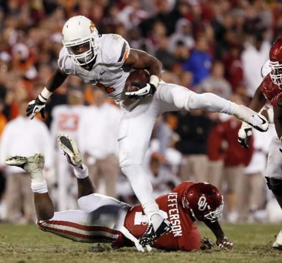 Oklahoma State's Joseph Randle (1) leaps over Oklahoma's Tony Jefferson (1) during the second half of the Bedlam college football game in which the University of Oklahoma Sooners (OU) defeated the Oklahoma State University Cowboys (OSU) 51-48 in overtime at Gaylord Family-Oklahoma Memorial Stadium in Norman, Okla., Saturday, Nov. 24, 2012. Photo by Steve Sisney