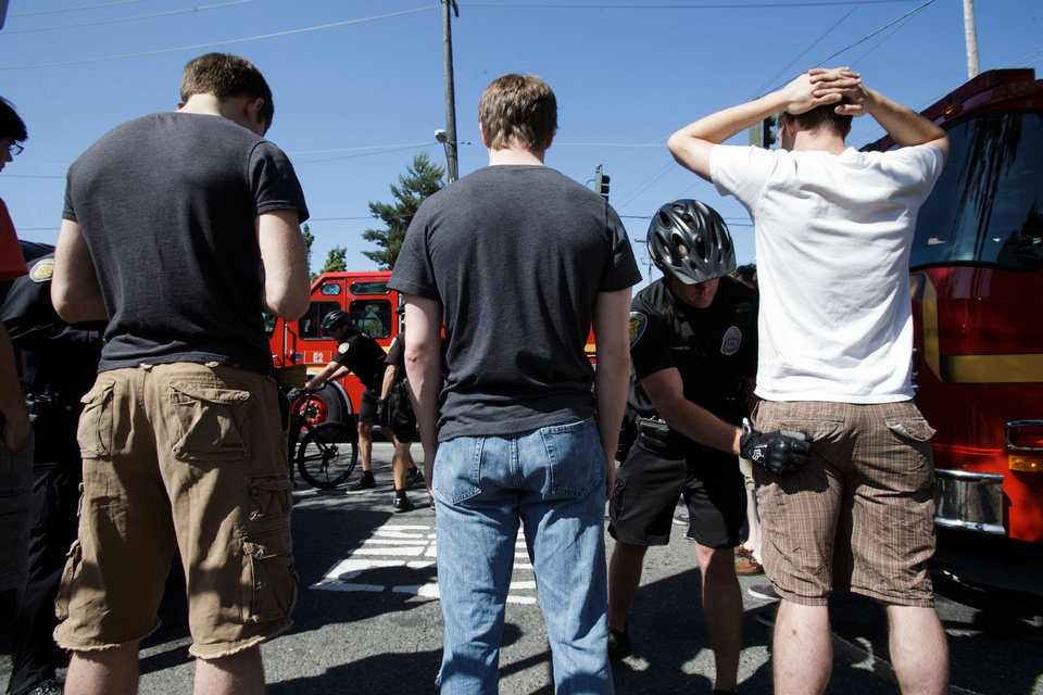 Photo - Police officers conduct body searches on students after a shooting occurred on the Seattle Pacific University campus Thursday, June 5, 2014, in Seattle. The university posted online Thursday that
