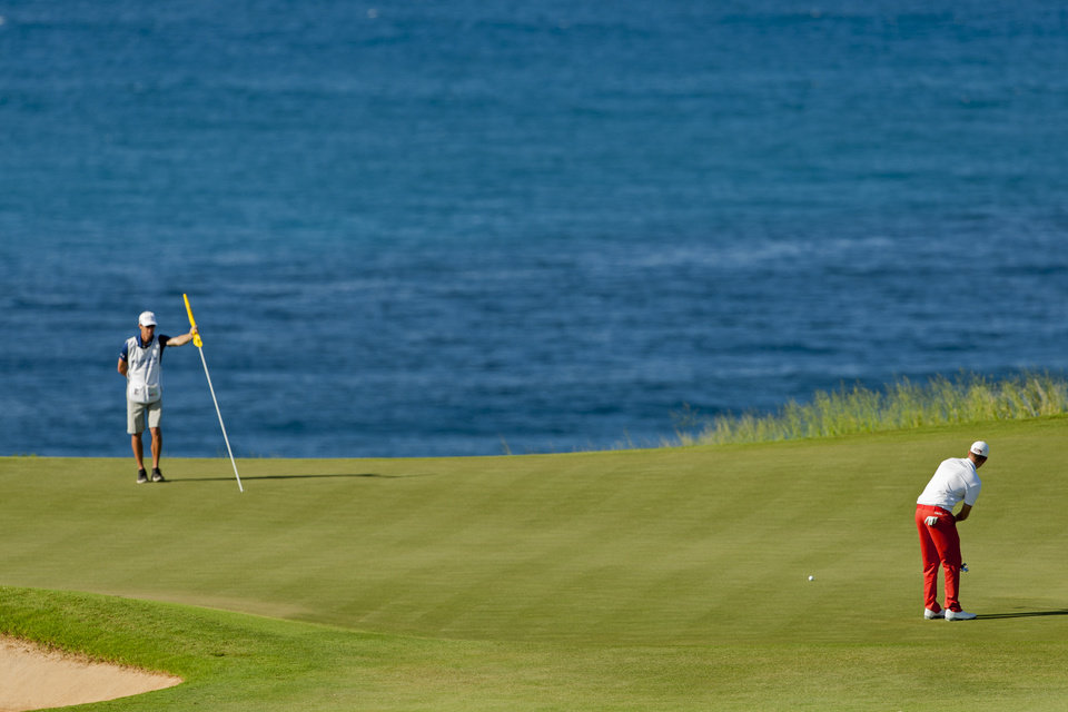 Photo - Caddie Ted Scott, left, holds the pin over the hole as Webb Simpson putts on the 11th green during the third round of the Tournament of Champions golf tournament, Sunday, Jan. 5, 2014, in Kapalua, Hawaii. (AP Photo/Marco Garcia)