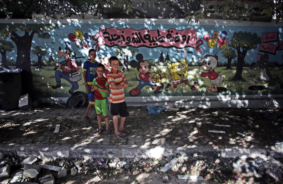 Photo - Palestinian boys stand next to wall with murals and Arabic writing that reads