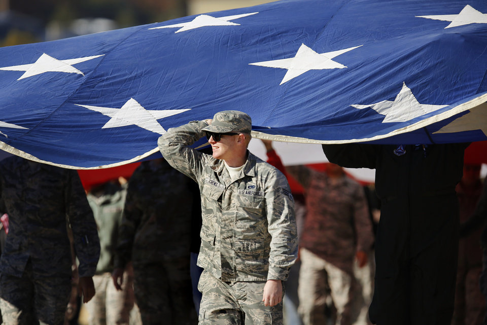 Photo - This airman was one of more than 100 volunteers who carried a large American flag along the route of the Midwest City Veteran's Day Parade on Friday, Nov. 10, 2017. Photo by Jim Beckel, The Oklahoman