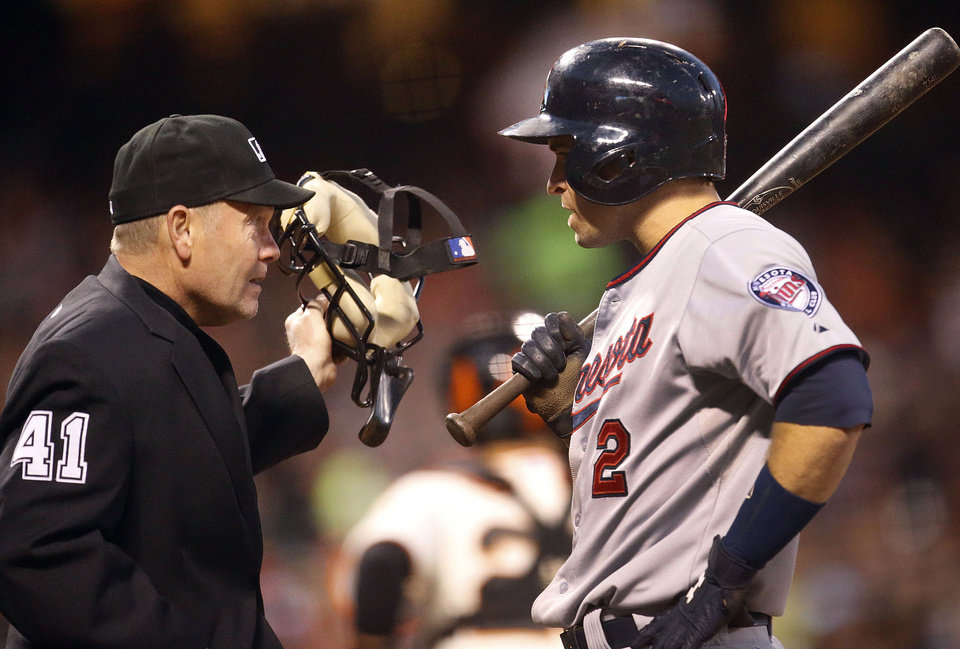 Photo - Minnesota Twins' Brian Dozier (2) argues with home plate umpire Jerry Meals after striking out against the San Francisco Giants in the fifth inning of a baseball game Saturday, May 24, 2014, in San Francisco. (AP Photo/Tony Avelar)