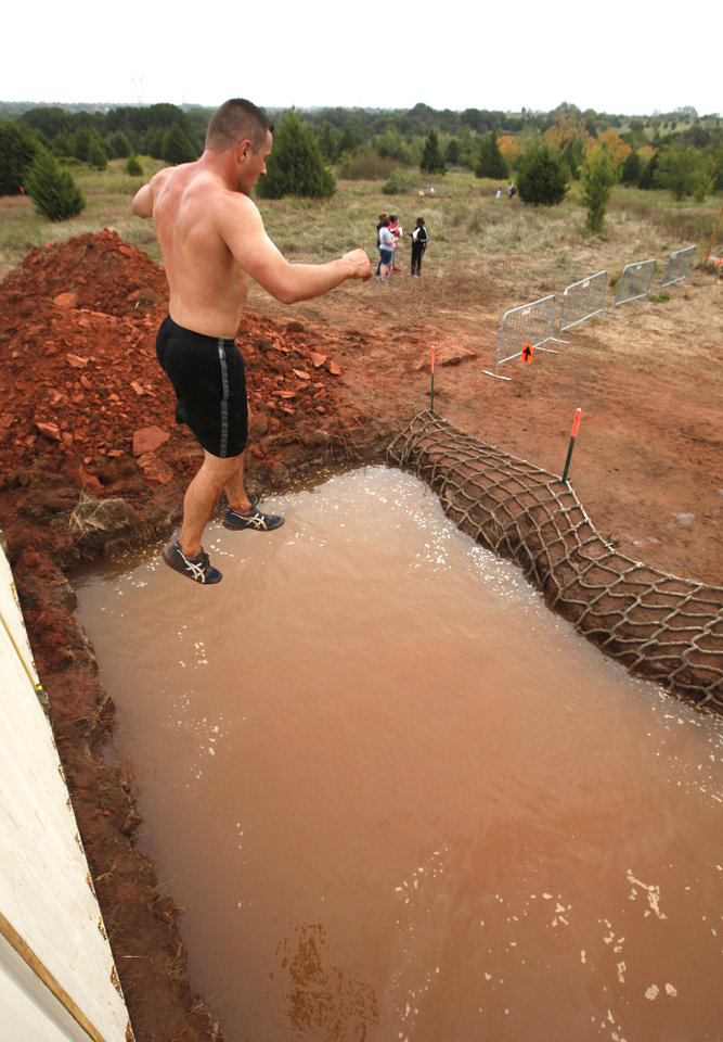 Luke Gregory jumps into a water filled pit during the Juggernaut mud run at Mitch Park, in Edmond, OK, Saturday, September 29, 2012. The Juggernaut is part of a national mud run series to raise money for Susan G. Komen for the Cure. By Paul Hellstern, The Oklahoman