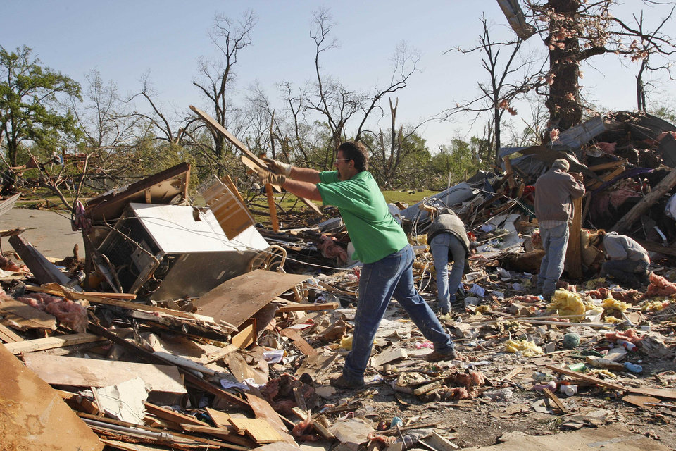Stephen Eldridge throws rubble on a pile as he helps clean up the remains of two relatives homes, in Tushka, Okla., Friday, April 15, 2011. The home crashed together during last night's tornadoes. (AP Photo/Sue Ogrocki)