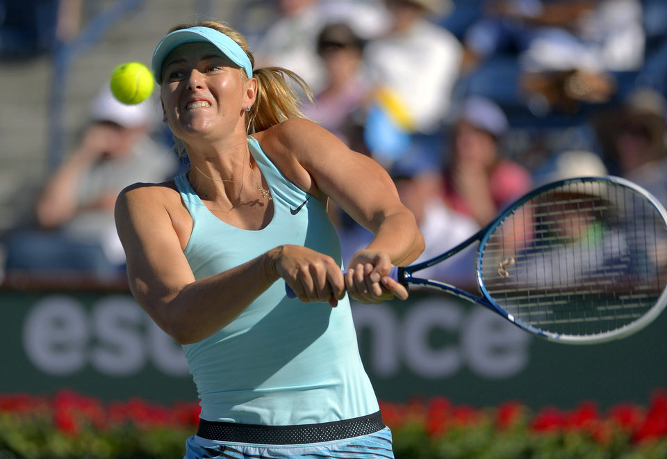 Photo - Maria Sharapova, of Russia, hits to Camila Giorgi, of Italy, during a third round match at the BNP Paribas Open tennis tournament, Monday, March 10, 2014, in Indian Wells, Calif. (AP Photo/Mark J. Terrill)