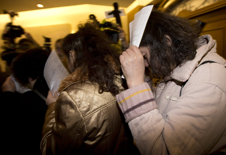 Photo - Chinese relatives of passengers aboard a missing Malaysia Airlines plane use application documents to block their faces as they walk out a hotel room in Beijing Monday, March 10, 2014. The anguished hours had turned into a day and a half. Fed up with awaiting word on the missing plane, relatives of passengers in Beijing lashed out at the carrier with a handwritten ultimatum and an impromptu news conference. (AP Photo/Andy Wong)