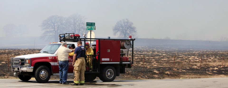 Photo - Fred Anderson, far left, Okla. City, talks with firefighters at Wilshire and Post Road as a grass fire burns around his home in the background in Oklahoma City Wednesday, April 6, 2011. Photo by Paul B. Southerland, The Oklahoman