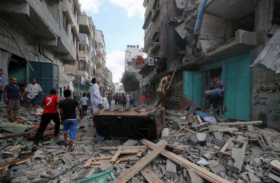 Photo - Palestinians inspect the rubble of a building to pick up their usable belongings after it was hit by an Israeli missile strike in Gaza City, Friday, July 18, 2014. Israeli troops pushed deeper into Gaza on Friday to destroy rocket launching sites and tunnels, firing volleys of tank shells and clashing with Palestinian fighters in a high-stakes ground offensive meant to weaken the enclave's Hamas rulers. (AP Photo/Hatem Moussa)