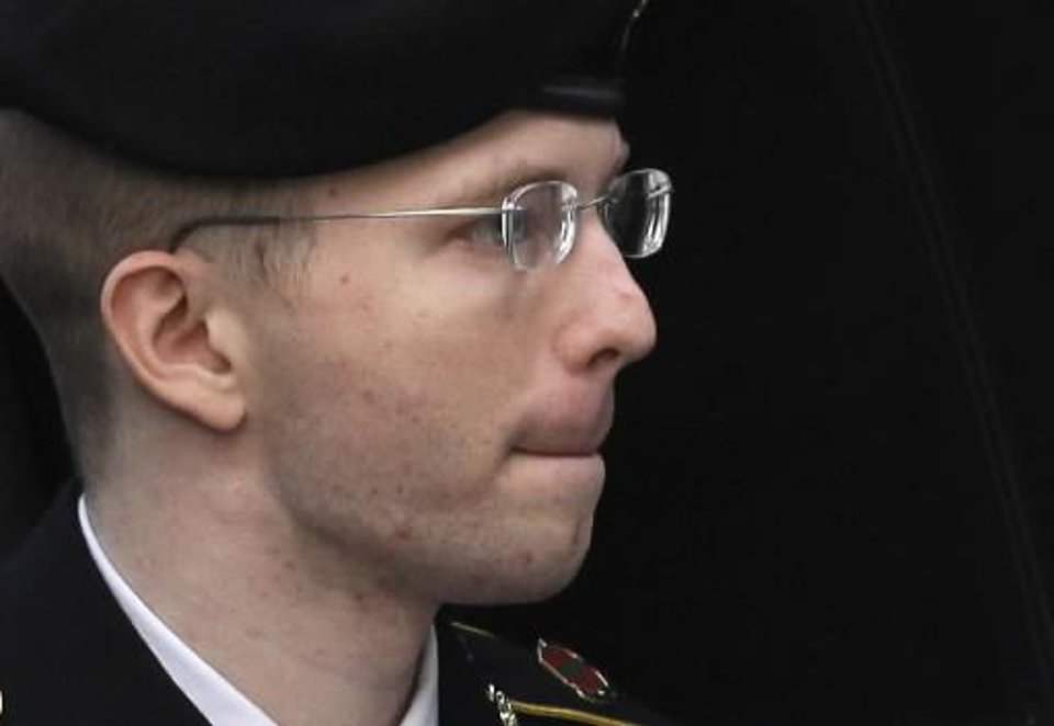 Photo - Army Pfc. Bradley Manning is escorted into a courthouse in Fort Meade, Md., Wednesday, Aug. 21, 2013, before a sentencing hearing in his court martial. The military judge overseeing Manning's trial sentenced Bradley Manning to 35 years in prison for giving US secrets to WikiLeaks. (AP Photo/Patrick Semansky)