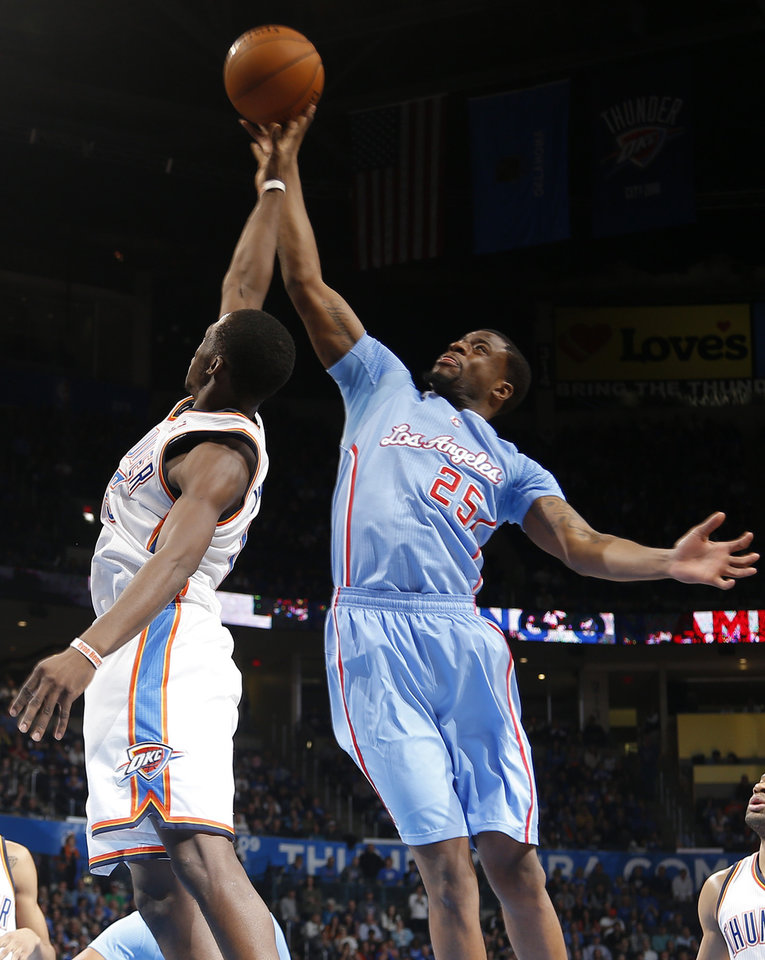 Photo - Los Angeles' Reggie Bullock (25) shoots over Oklahoma City 's Reggie Jackson (15) during the NBA game between the Oklahoma City Thunder and the Los  Angeles Clippers at the Chesapeake Energy Arena, Sunday, Feb. 23, 2014. Photo by Sarah Phipps, The Oklahoman
