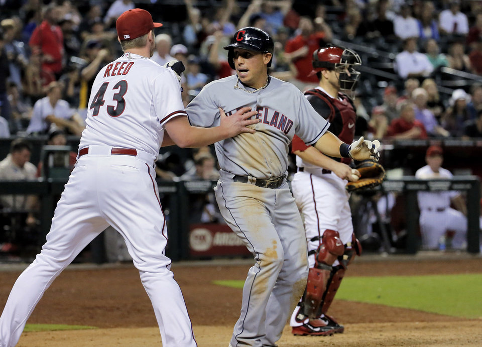 Photo - Cleveland Indians' Asdrubal Cabrera, center, collides with Arizona Diamondbacks pitcher Addison Reed (43) as Miguel Montero looks away after Cabrera scored during the ninth inning of a baseball game, Tuesday, June 24, 2014, in Phoenix. (AP Photo/Matt York)