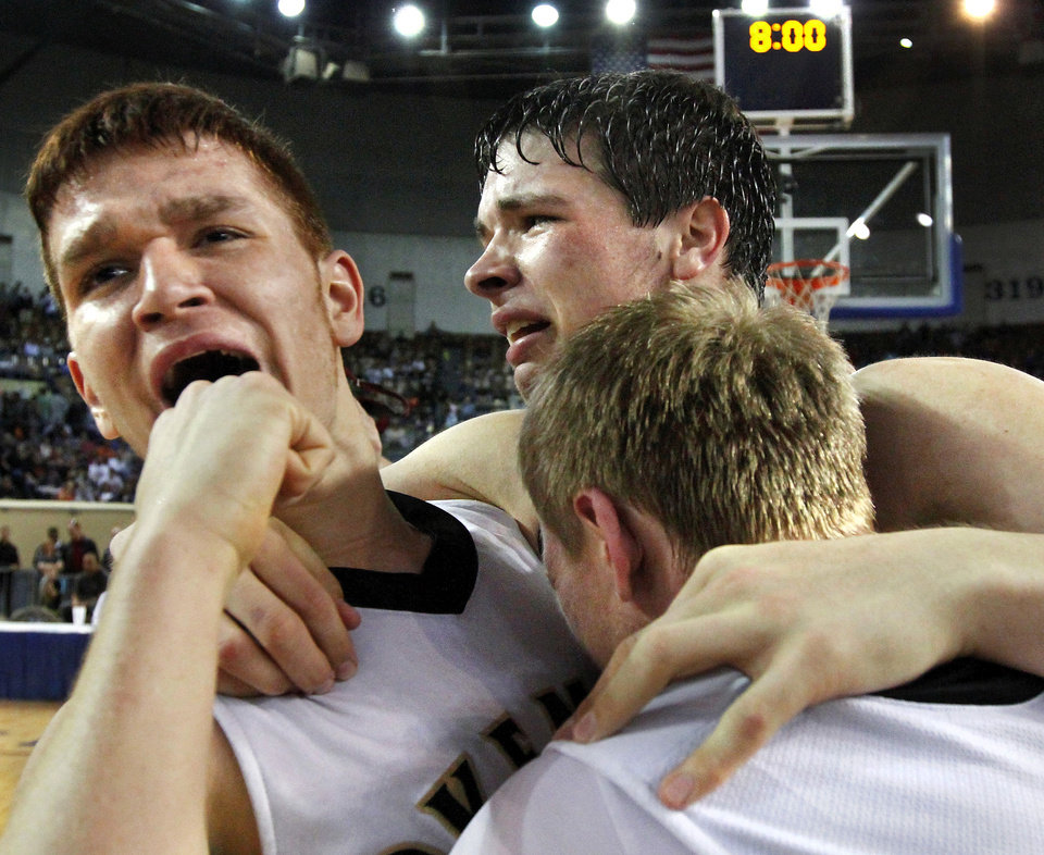 Photo - Physically exhausted from a double overtime win, Okemah players, from left, Matt Dunson, #23, Austin Guinn, #35, and Gus Klutts, #20,  find enough strength to support each other while  they celebrate at the end of the Class 3A Boys State Championship game between Oklahoma Centennial and Okemah at Jim Norick Arena at State Fair Park  on Saturday, Mar. 15, 2014. Okemah outlasted the Bison, winning in double overtime, 54-53. Photo by Jim Beckel, The Oklahoman