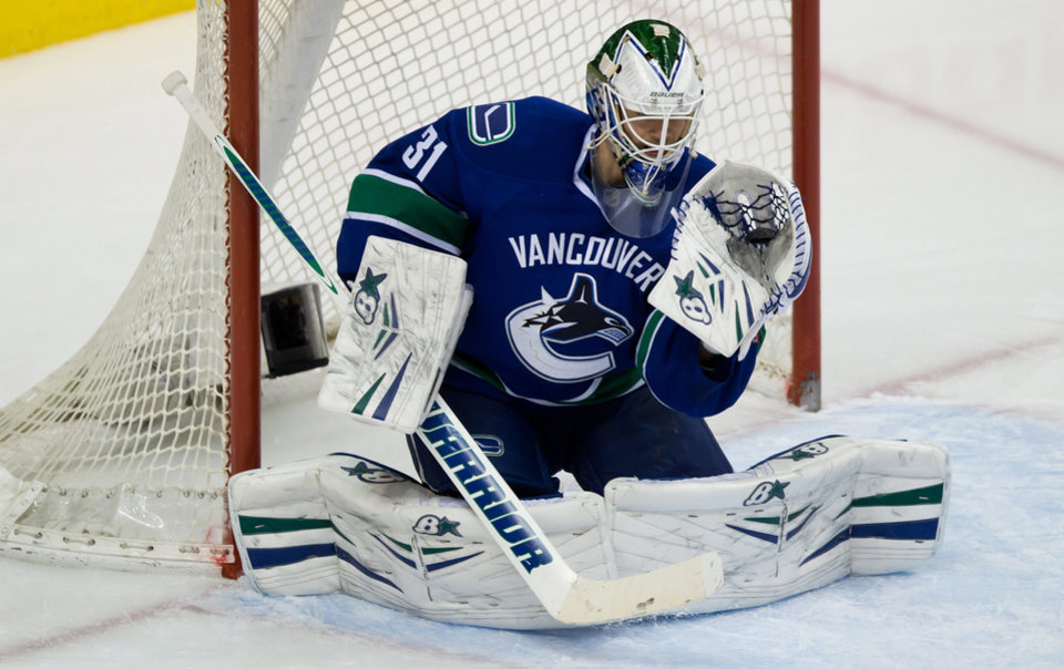 Photo - Vancouver Canucks goalie Eddie Lack, of Sweden, makes a glove save against the Nashville Predators during the second period of an NHL hockey game Wednesday, March 19, 2014. (AP Photo/The Canadian Press, Darryl Dyck)