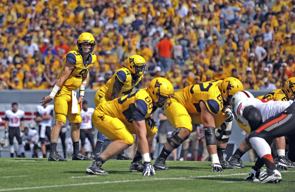 Photo - West Virginia quarterback Clint Trickett (9) signals his reciever during the second quarter of an NCAA college football game against Oklahoma State in Morgantown, W.Va., on Saturday, Sept. 28, 2013. (AP Photo/Tyler Evert) ORG XMIT: WVTE307