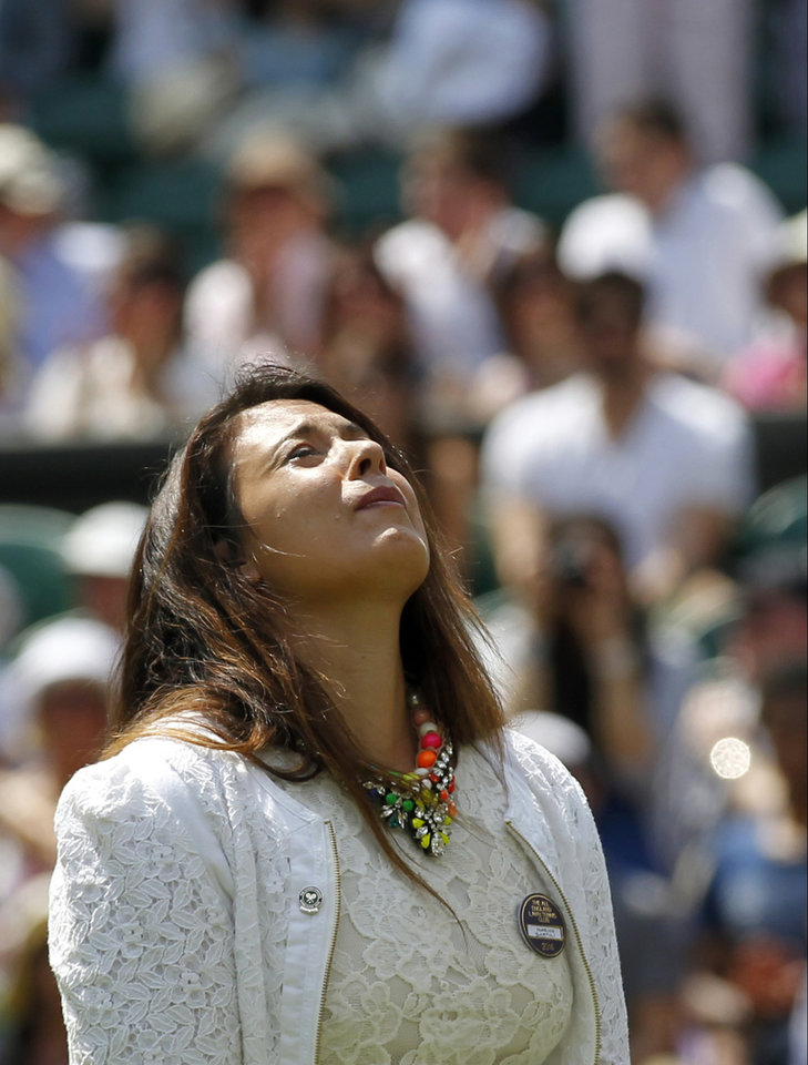 Photo - 2013 Wimbledon champion Marion Bartoli of France looks up as she takes part in the coin toss for the match between Julia Glushko of Israel and Sabine Lisicki of Germany at the All England Lawn Tennis Championships in Wimbledon, London, Tuesday, June 24, 2014. Traditionally the reigning champion would play her first match on Centre Court but due to Bartoli's retirement the runner up Lisicki will open play. (AP Photo/Sang Tan)
