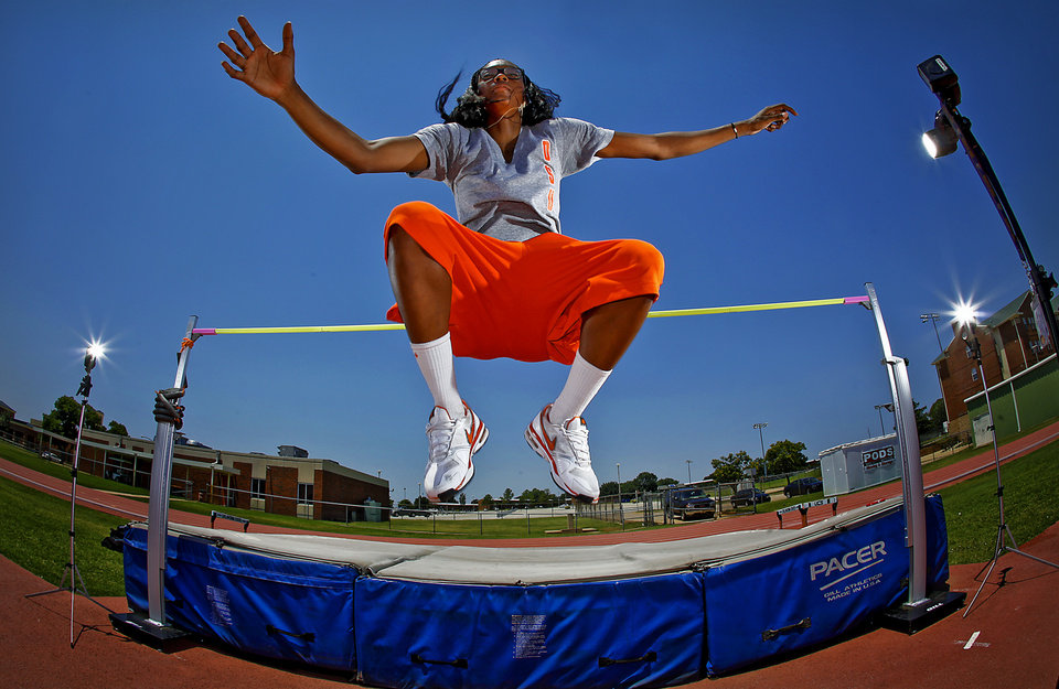 Photo - Oklahoma State women's basketball player Toni Young poses for a photo at the high-jump bar in Stillwater, Okla. Monday, June 25, 2012. Young qualified for the U.S. Olympic track and field trials after deciding on a whim to give the high-jump a try.  Photo by Chris Landsberger, The Oklahoman