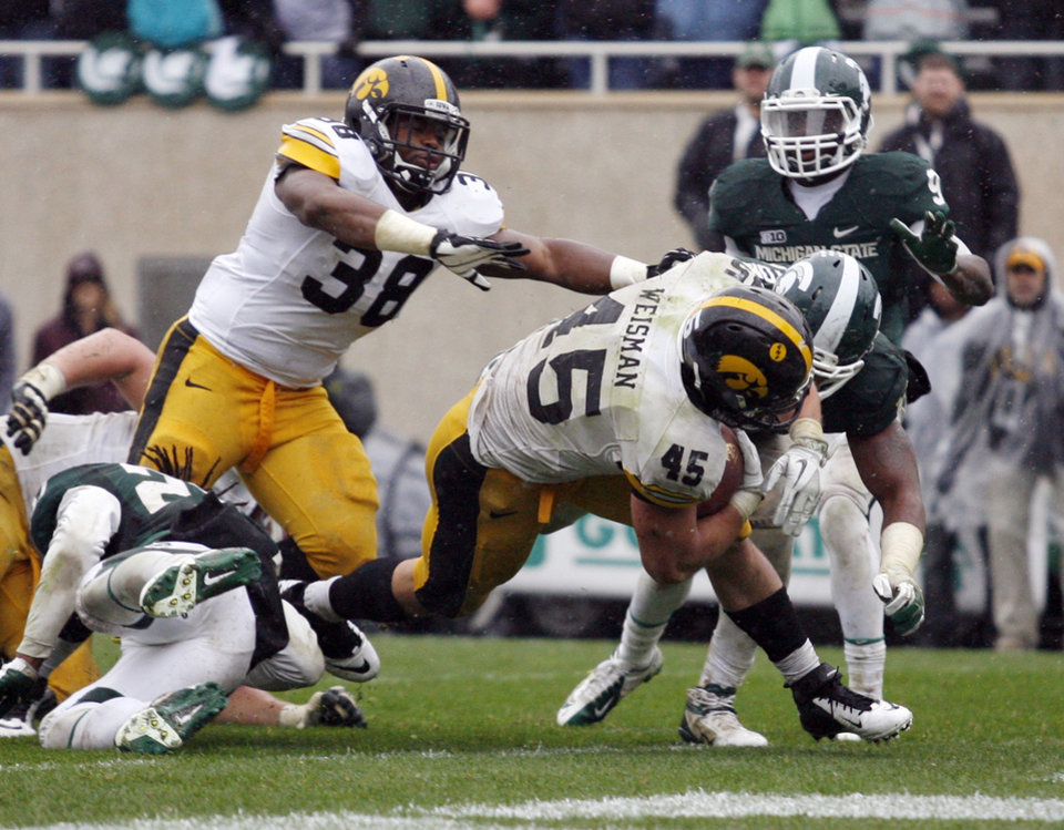 Iowa's Mark Weisman (45) scores a touchdown against Michigan State's William Gholston, right, and Kurtis Drummond, left, as Iowa's Brad Rogers (38) trails with less than a minute remaining in the fourth quarter of an NCAA college football game, Saturday, Oct. 13, 2012, in East Lansing, Mich. The extra point tied the score and Iowa won 19-16 in double overtime. (AP Photo/Al Goldis)