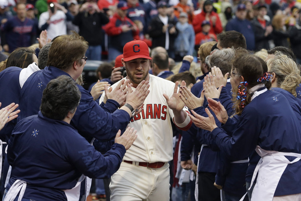 Photo - Cleveland Indians' Jason Kipnis gives high-fives during introductions before a baseball game between the Minnesota Twins and the Cleveland Indians, Friday, April 4, 2014, in Cleveland. (AP Photo/Tony Dejak)