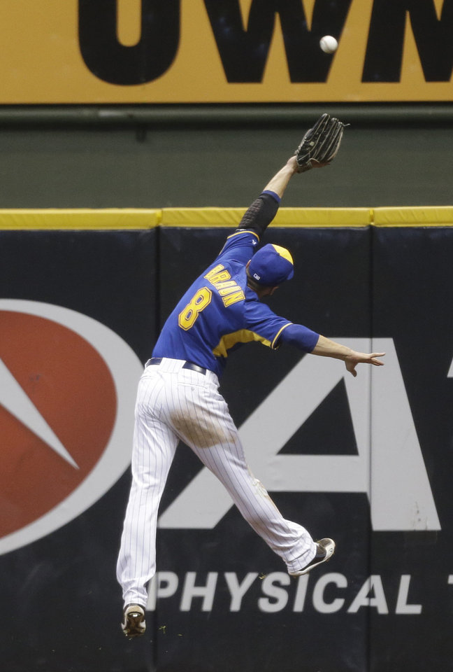 Photo - Milwaukee Brewers' Ryan Braun leaps but can't catch a double by St. Louis Cardinals Matt Holliday during the fourth inning of a baseball game Friday, July 11, 2014, in Milwaukee. (AP Photo/Jeffrey Phelps)