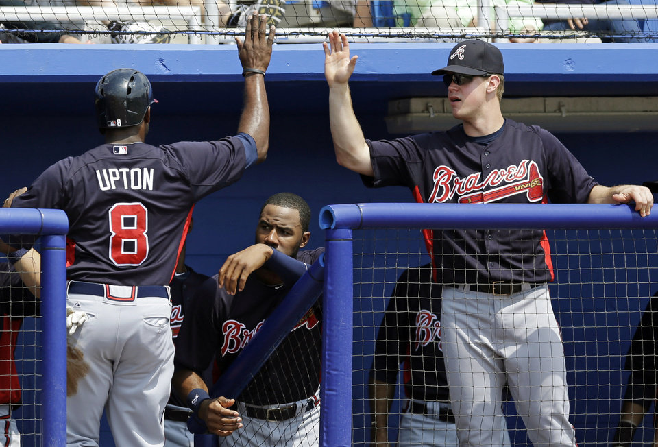 Teammates greet Atlanta Braves Justin Upton (8) after he scored on Emilio Bonifacio\'s throwing error in the second inning of a spring training baseball game against the Toronto Blue Jays in Dunedin, Fla., Saturday, March 23, 2013. The Braves Jayson Heyward, center, watches. (AP Photo/Kathy Willens)