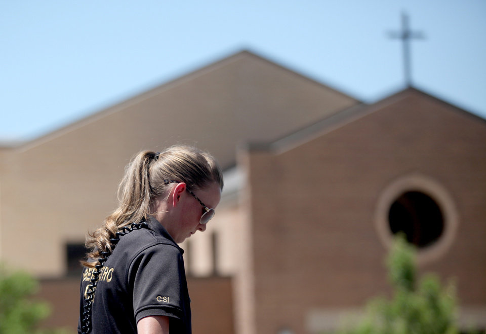 Photo - Crime scene investigators examiner the parking lot outside of St. James Catholic Church in Ogden, Utah, where a man was shot in the back of the head during Sunday Mass on June 16, 2013.   Charles Richard Jennings Jr., 35, was arrested Sunday afternoon in nearby Box Elder County after fleeing in a stolen pickup truck, investigators said.  (AP Photo/Standard-Examiner, Benjamin Zack) TV OUT; MANDATORY CREDIT