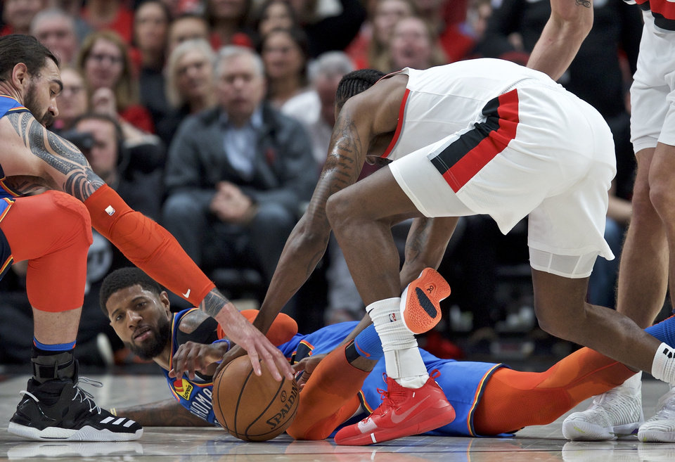 Photo - Oklahoma City Thunder forward Paul George, center, and center Steven Adams, left, and Portland Trail Blazers forward Al-Farouq Aminu dive for a loose ball during the second half of Game 2 of an NBA basketball first-round playoff series Tuesday, April 16, 2019, in Portland, Ore. (AP Photo/Craig Mitchelldyer)