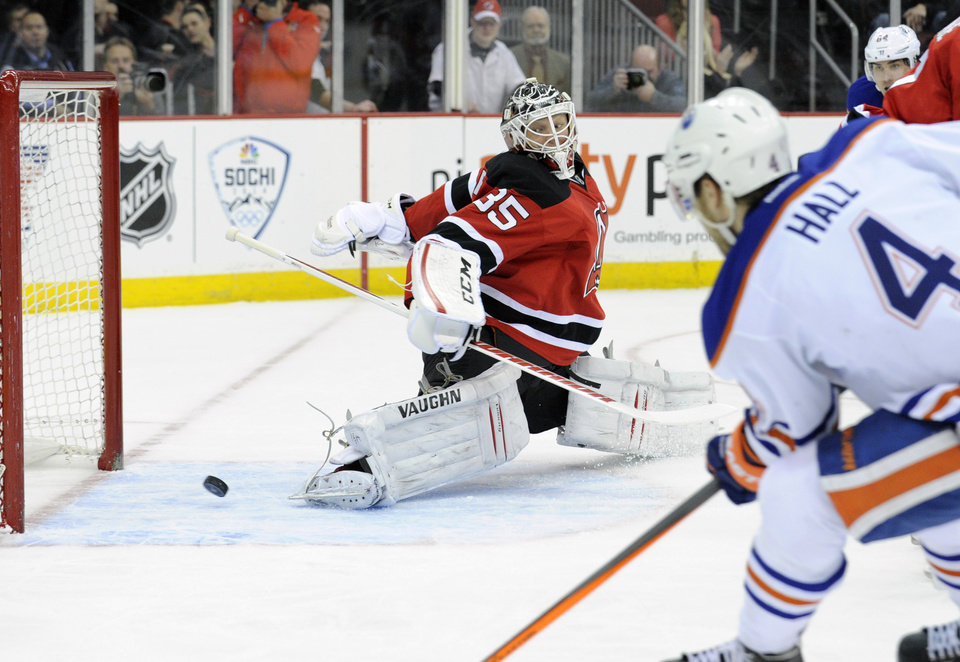 Photo - Edmonton Oilers' Taylor Hall (4) scores a goal past New Jersey Devils goaltender Cory Schneider during the first period of an NHL hockey game, Friday, Feb. 7, 2014, in Newark, N.J. (AP Photo/Bill Kostroun)