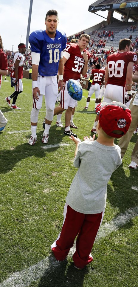 Photo - Quarterback Blake Bell plays catch with a young fan after the annual Spring Football Game at Gaylord Family-Oklahoma Memorial Stadium in Norman, Okla., on Saturday, April 13, 2013. Photo by Steve Sisney, The Oklahoman