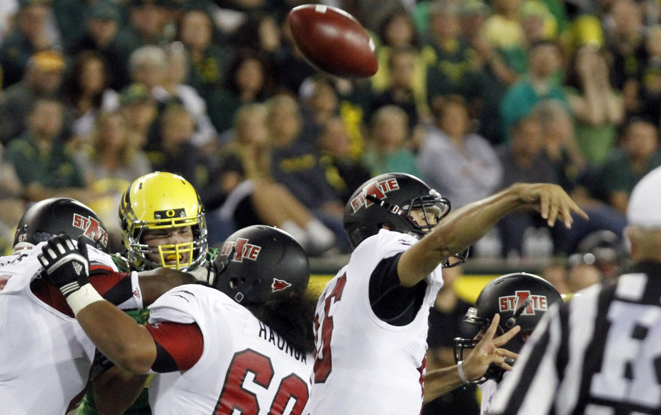 Photo -   Arkansas State quarterback Ryan Aplin loses his grip on the ball while passing during the first half of their NCAA college football game against Oregon in Eugene, Ore., Saturday, Sept. 1, 2012. Aplin recovered his fumble on this play.(AP Photo/Don Ryan)